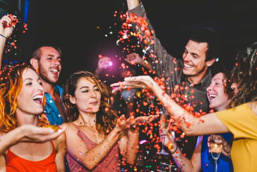 Happy friends doing party throwing confetti in the club - Millennial young people having fun celebrating in the nightclub - Nightlife, entertainment and youth festive holidays concept