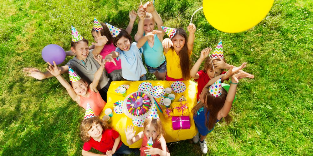 Top view of laughing kids standing around the table with birthday cake, waving hands and balloons, at the outdoor party